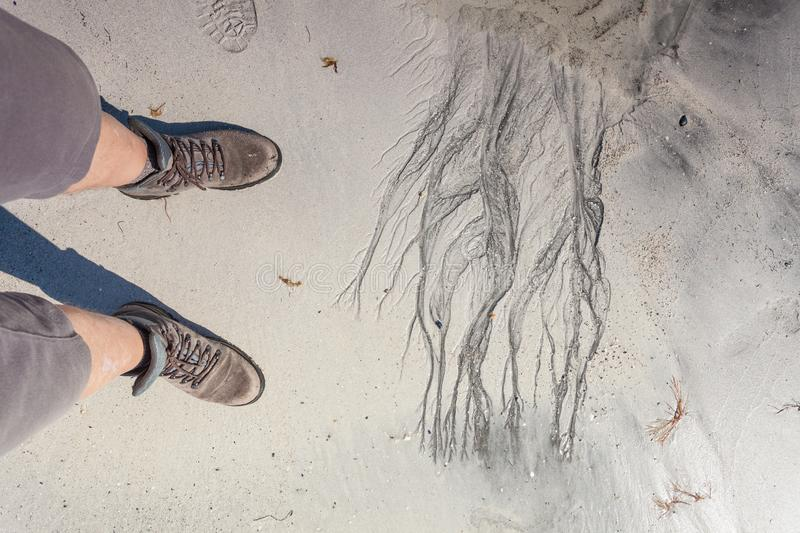 Male feet in hiking shoes on beach. Male feet in hiking shoes on sandy beach. Summertime royalty free stock photography