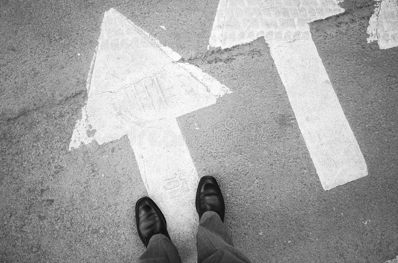 Male feet in new black shoes stand on asphalt. Male feet in new black shining leather shoes stand on asphalt pavement with white arrows pedestrian crossing road stock image