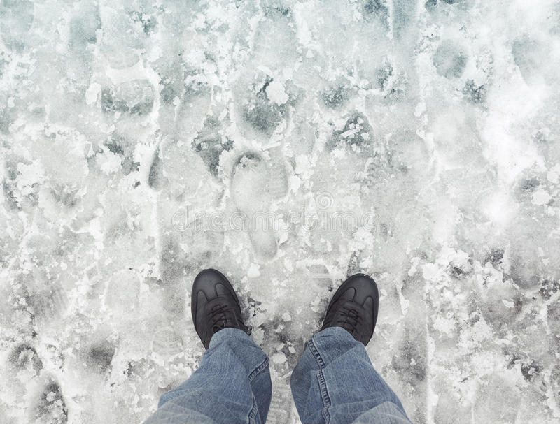 Male feet in new shoes stand on wet dirty snow royalty free stock image