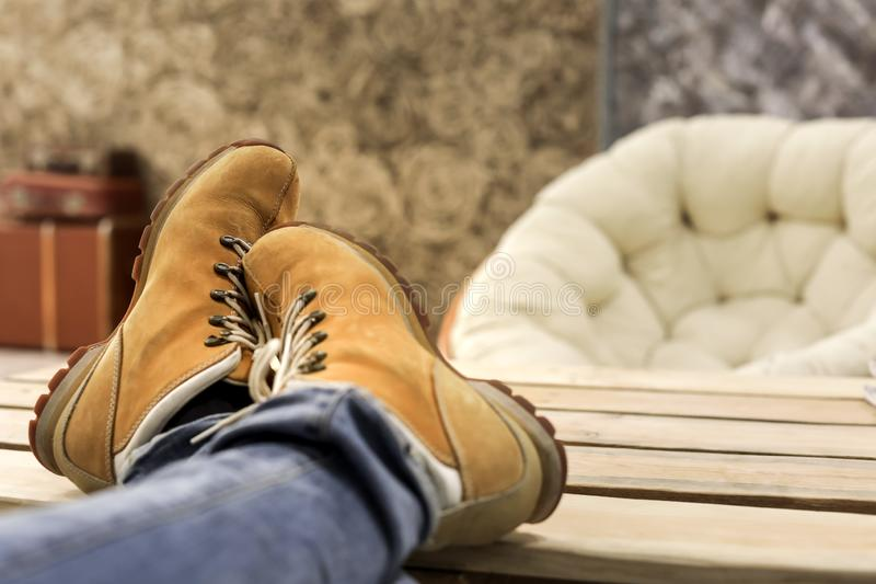 Male feet with orange shoes relaxing on wooden table. In room stock photos