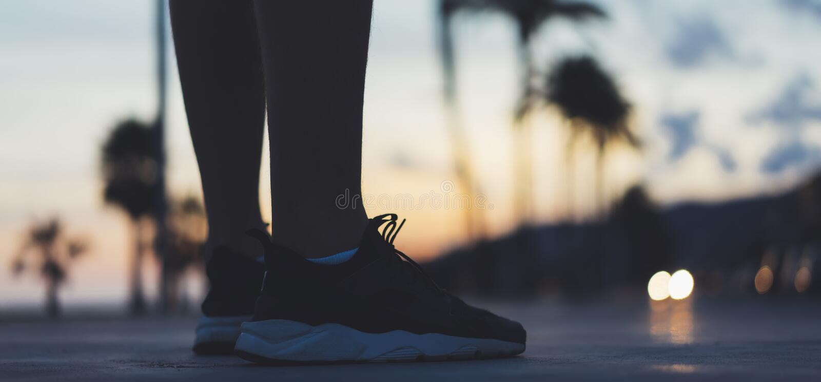 Male feet with sneakers close up on background sunset or sunrise nature outdoor, sports man running marathon, workout style royalty free stock photography
