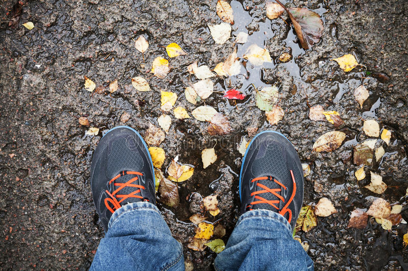 Male feet in sport shoes standing on dirty road stock photo