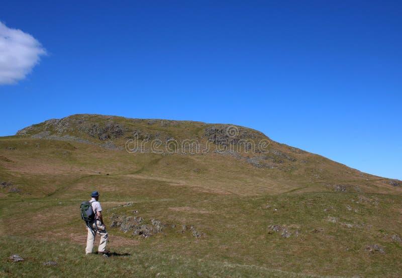 Male fellwalker on slopes of Hallin Fell, Cumbria. Male senior fellwalker with rucksack on footpath on slopes of Hallin Fell, in the English Lake District royalty free stock photos