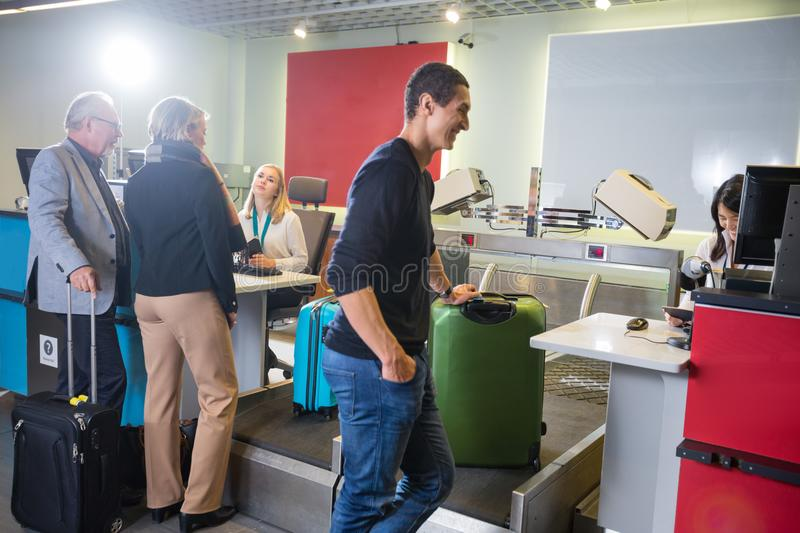 Airline Passengers Weighting Their Baggage At Airport. Male and female airline passengers weighting their baggage at airport check-in desk royalty free stock photo