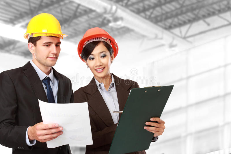 Male and female architect at construction site stock photo