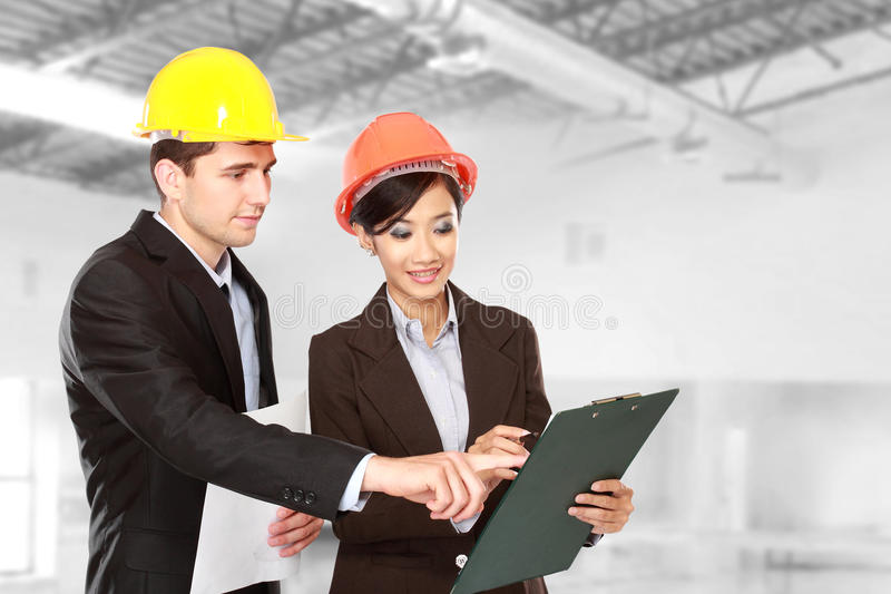 Male and female architect at construction site royalty free stock image