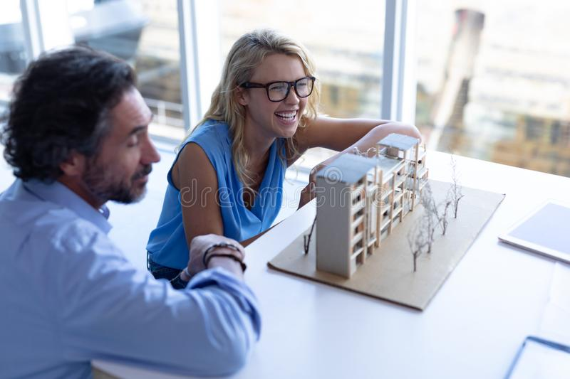 Male and female architect discussing over architectural model at table in a modern office royalty free stock images