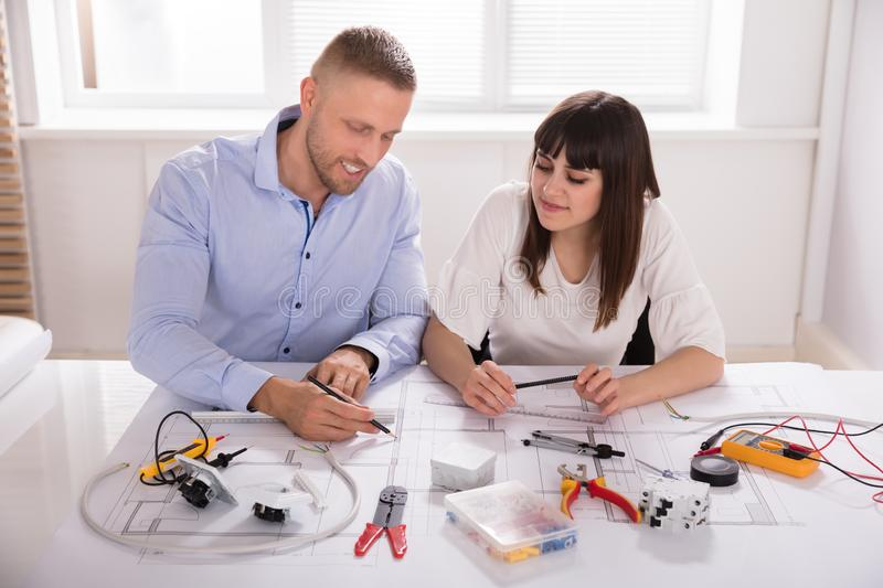 Male And Female Architect Working On Blueprint royalty free stock photography