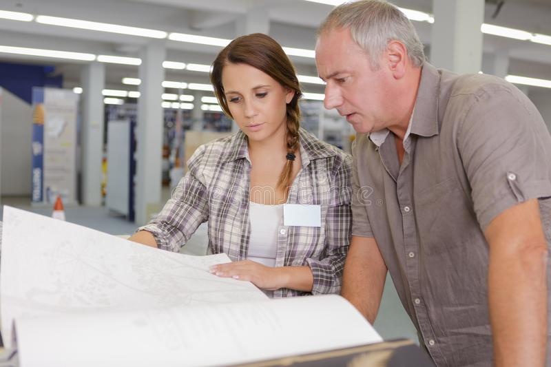 Male and female architects checking blueprints at construction site royalty free stock photography