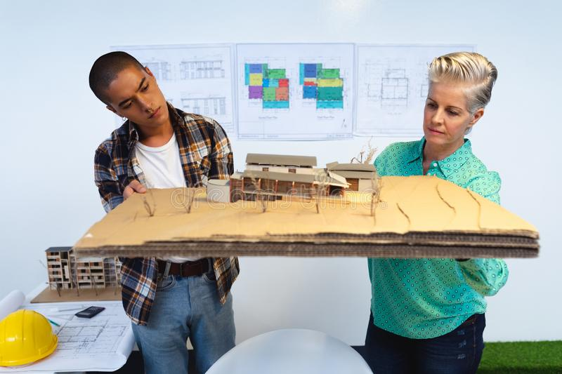Male and female architects looking at model structure of house stock photo