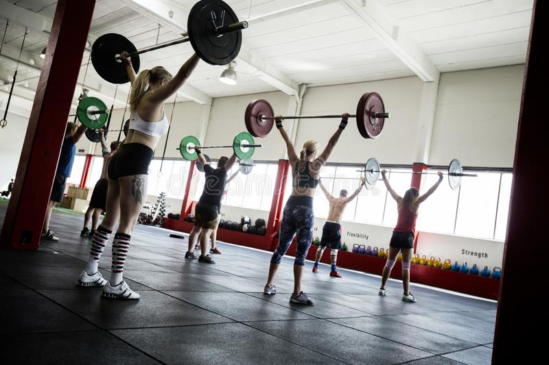 Male And Female Athletes Lifting Barbells stock images