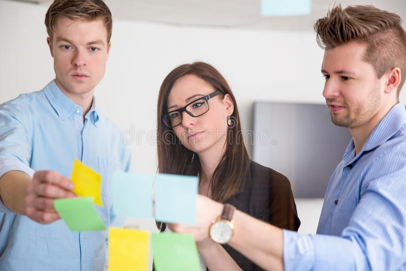 Business Colleagues Discussing Over Adhesive Notes Stuck On Glas royalty free stock images