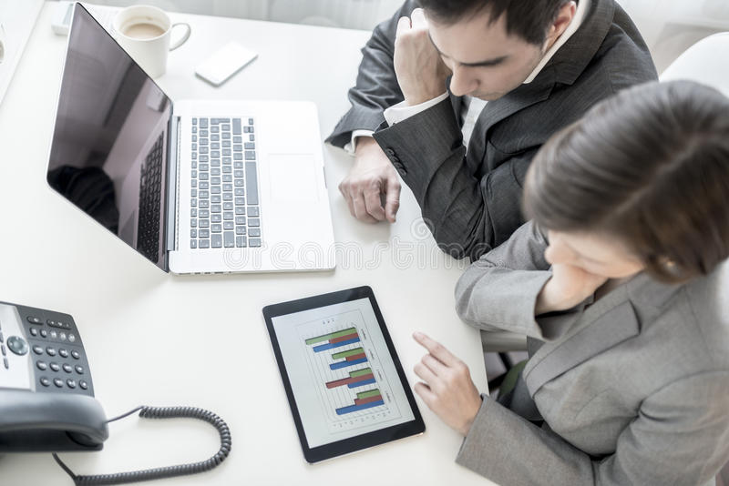 Male and female business partners analysing statistical annual r stock images