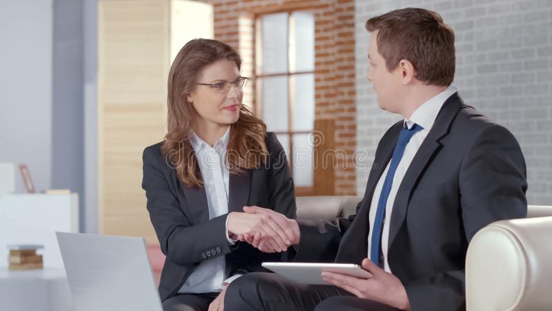 Male and female business partners come to successful agreement, shaking hands stock image