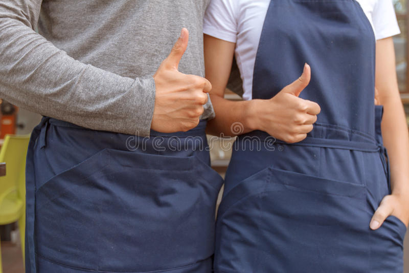 Male and female cafe workers thumbing up. Thumbing up. Portrait of mail and female cafeteria workers standing with thumbs up stock photo