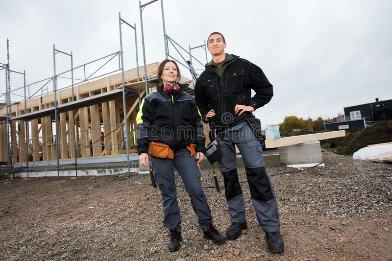 Male And Female Carpenters Against Incomplete Building. Low angle portrait of male and female carpenters against incomplete building stock image
