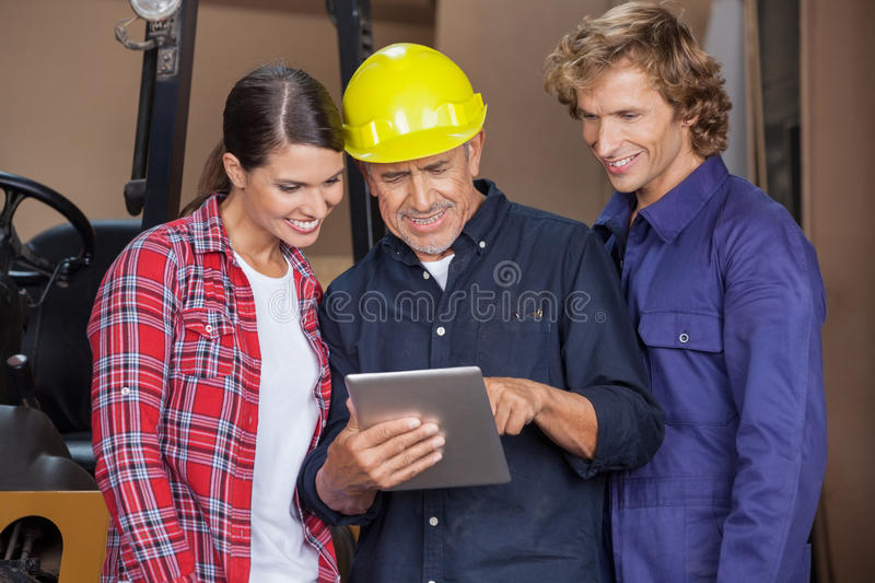 Male And Female Carpenters Using Digital Tablet stock images