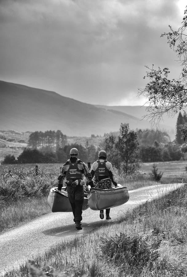 Carrying two canoes along narrow road. Glencoe, Scotland. royalty free stock image