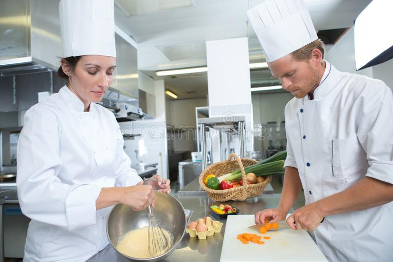 Male and female chef working at kitchen royalty free stock images