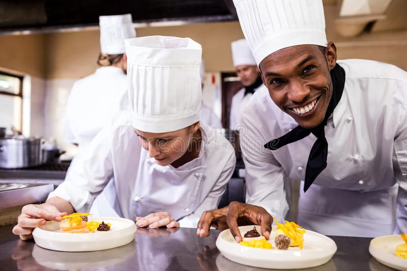 Male and female chefs garnishing delicious desserts in a plate royalty free stock photography