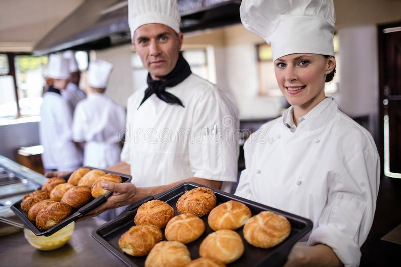 Male and female chefs holding baking tray of kaiser rolls in kitchen stock images