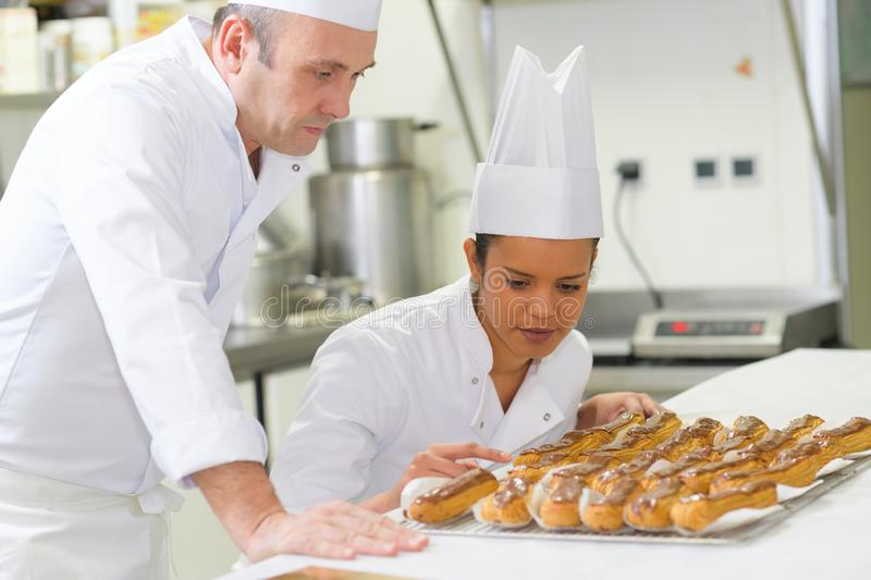 Male and female chefs looking at tray eclairs. Male and female chefs looking at tray of eclairs stock photos