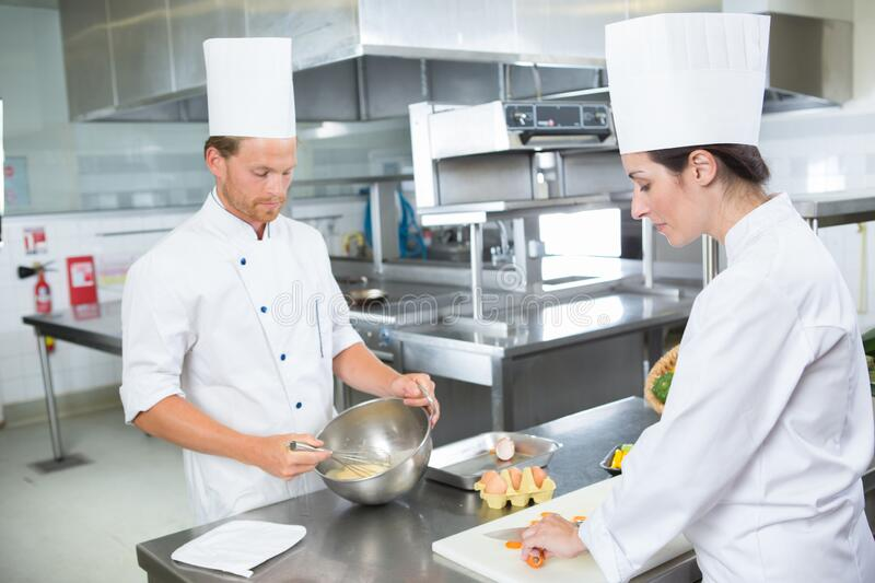 Male and female chefs preparing food in professional kitchen stock photo