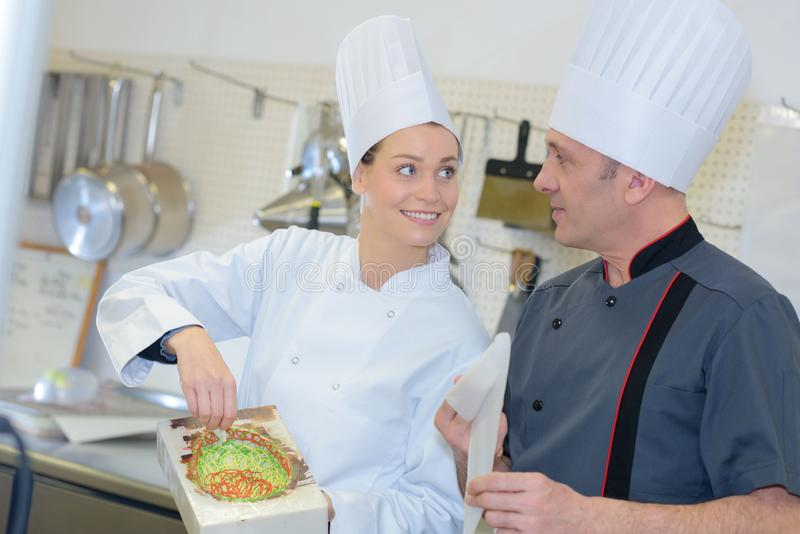 Male and female chefs working at kitchen stock photos