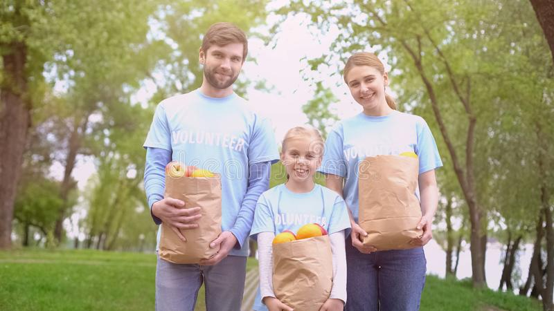 Male female and child volunteers holding paper bags with fruits, smiling camera stock photos