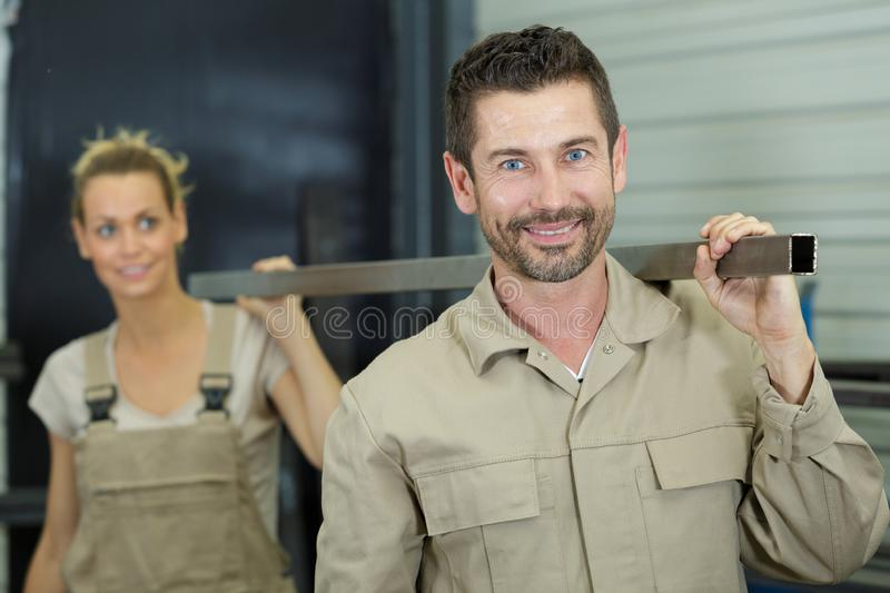 Male and female colleagues carrying metal length on their shoulders royalty free stock image