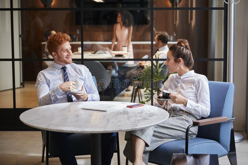 Male and female colleagues talk over coffee at office cafe stock image