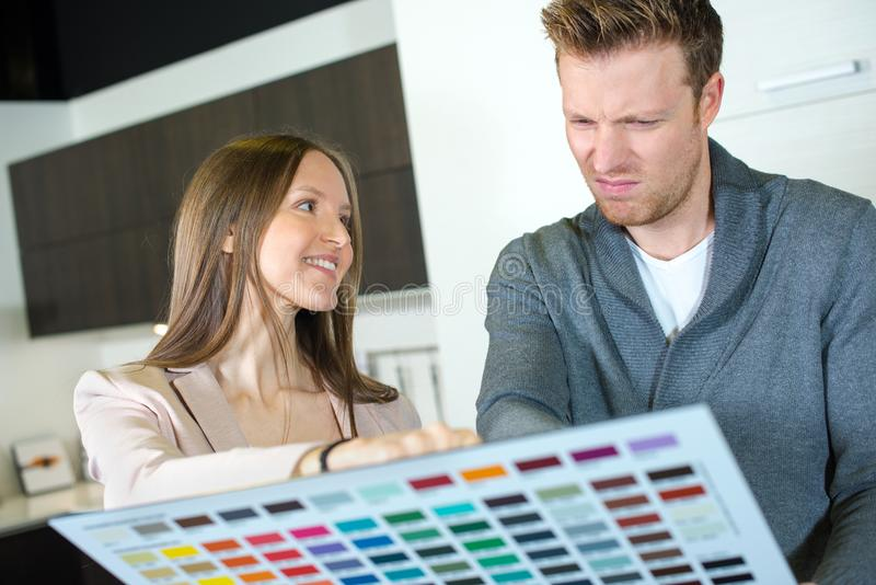Male and female collegues discussing colour samples stock photos