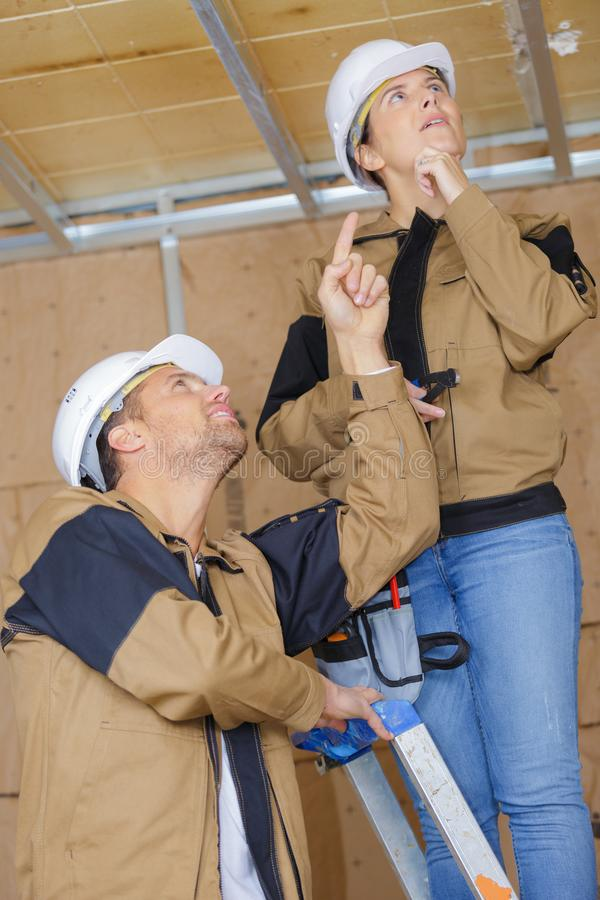 Male and female construction workers in wooden cabin at site royalty free stock image