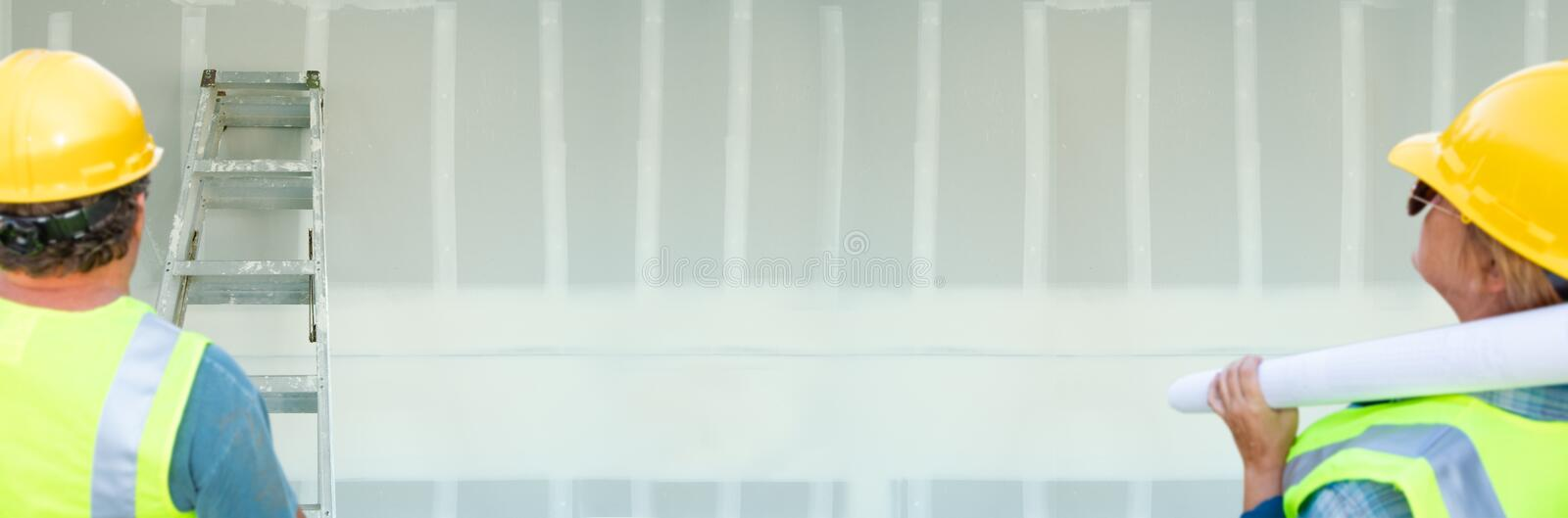 Male and Female Contractors Overlooking Blank Drywall Banner.  stock photo