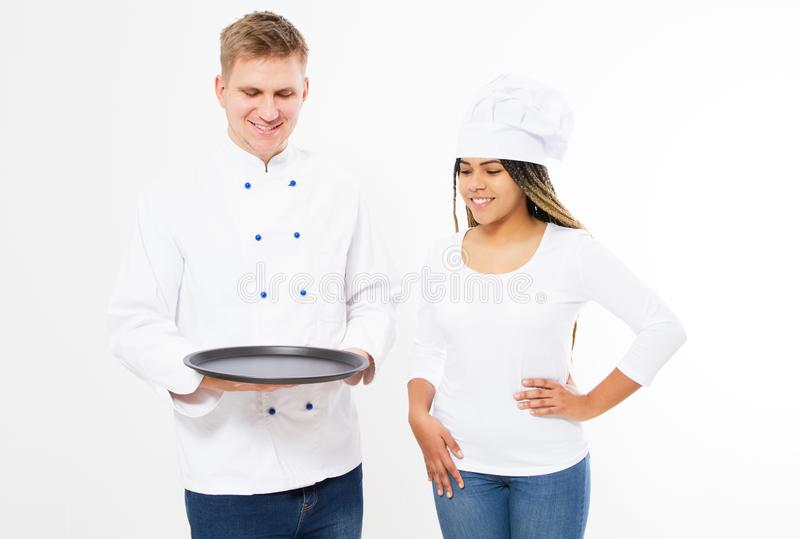 Male and female cooks in uniform hold empty tray isolated on white background.  stock photography