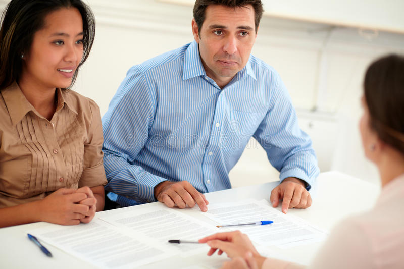 Male and female couple interested in a contract. Portrait of male and female couple interested in a contract sitting on office desk stock photos