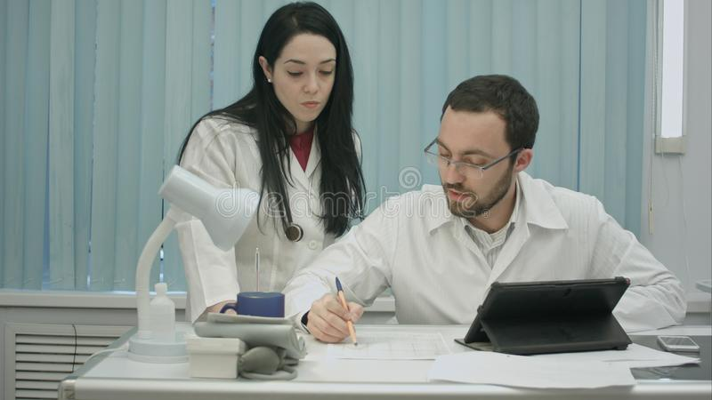 Male and female doctors discuss medical document royalty free stock photography