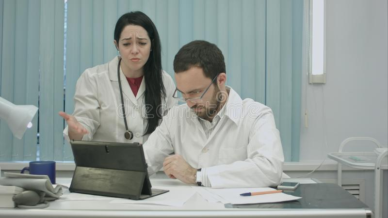 Male and female doctors discuss results useing tablet stock image