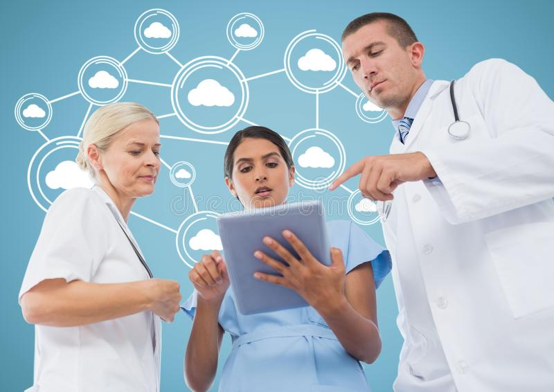 Male and female doctors discussing over digital tablet with cloud computing icons in background stock image