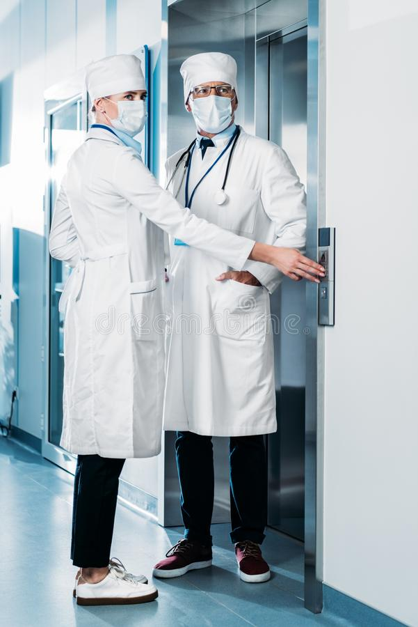 Male and female doctors in medicals masks pushing button of elevator in hospital. Corridor royalty free stock images
