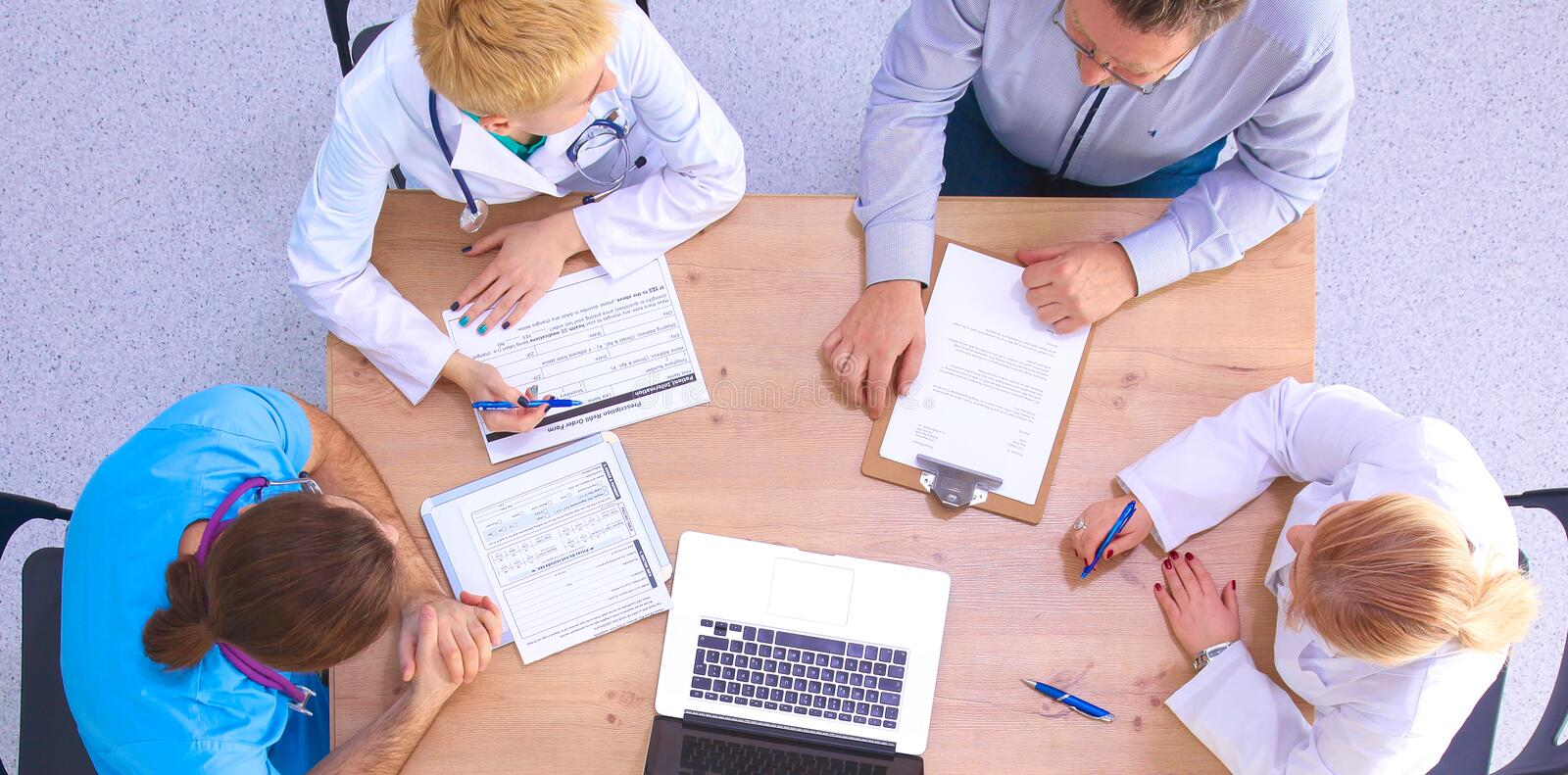 Male and female doctors working on reports in medical office.  royalty free stock image