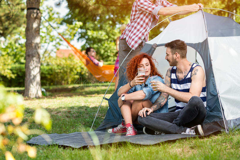 Male and female drinks beer in front of tent. Male and female at summer drinks beer in front of tent in forest royalty free stock photography