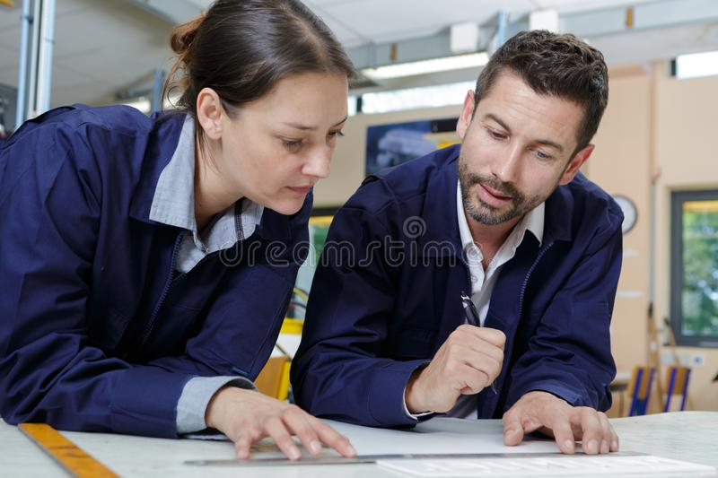 Male and female engineers in discussion over desk stock photos