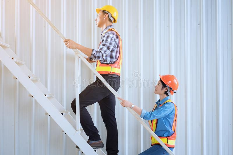 Male and female engineers are walk up the staurs for exploring t stock photos