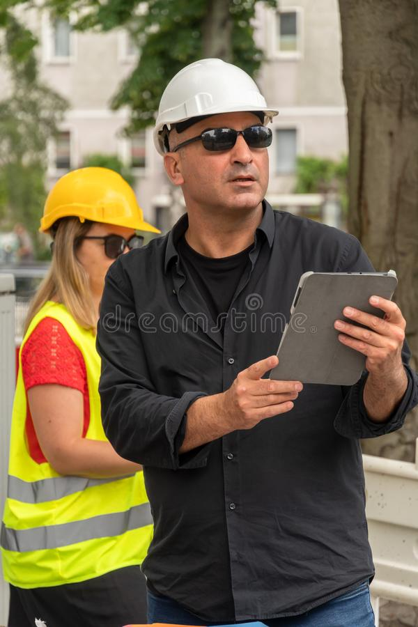 Male and female engineers at work on construction site. Absorbed engineers with protective helmets at work with documents and a tablet computer on construction royalty free stock images