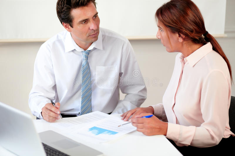 Male and female enterpreneur working on documents royalty free stock image