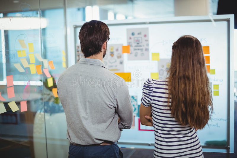 Male and female executives looking at whiteboard in office. Rear view of male and female executives looking at whiteboard in office royalty free stock photo