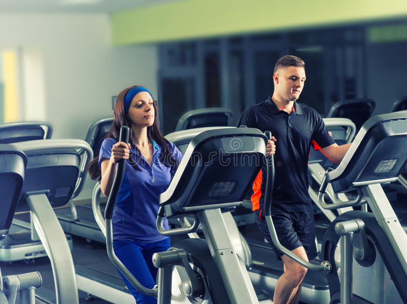 Male and female exercising on the crosstrainer machines stock photo