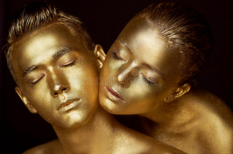 Male and female face around. The woman`s head lies on the shoulder of a man. All painted in gold paint, the feeling of a stock photo