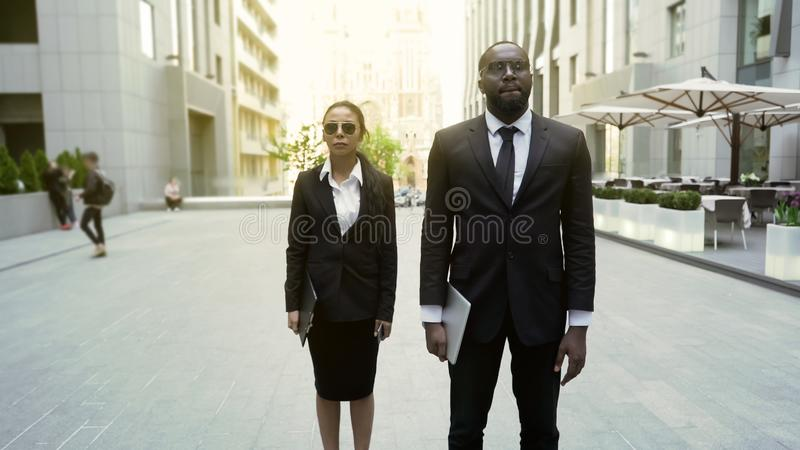 Male and female federal agents walking with warrant to arrest suspect, security stock photography